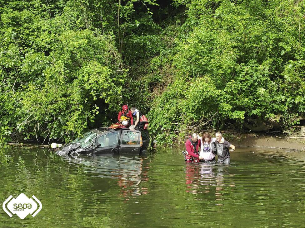 Los bomberos rescatan a los ocupantes del turismo que cayó al río