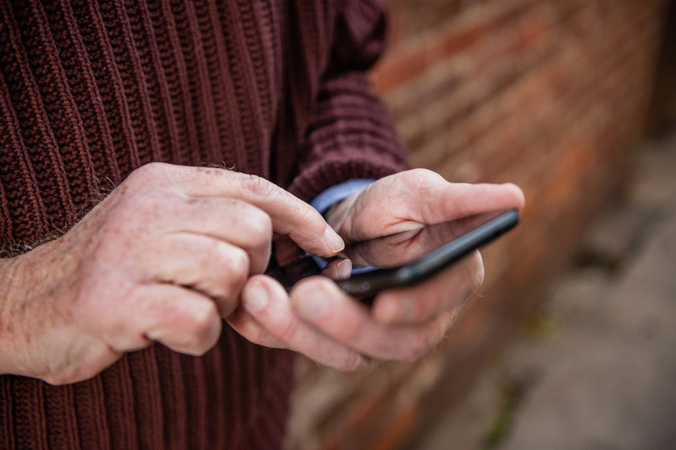 Hands of Senior Man Texting on Mobile Phone Outdoors in NYC USA