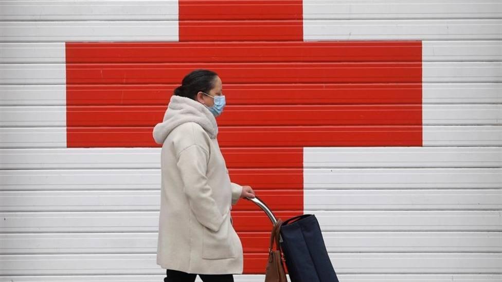 Una mujer pasa frente a la puerta de entrada de ambulancias de la Cruz Roja en Oviedo