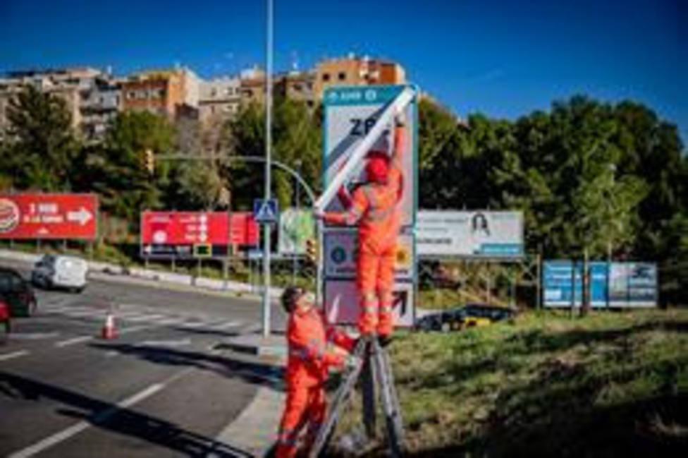 Operarios instalando las señales de tráfico definitivas de la ZBE Rondas BCN en el ramal de la salida 14 Besòs