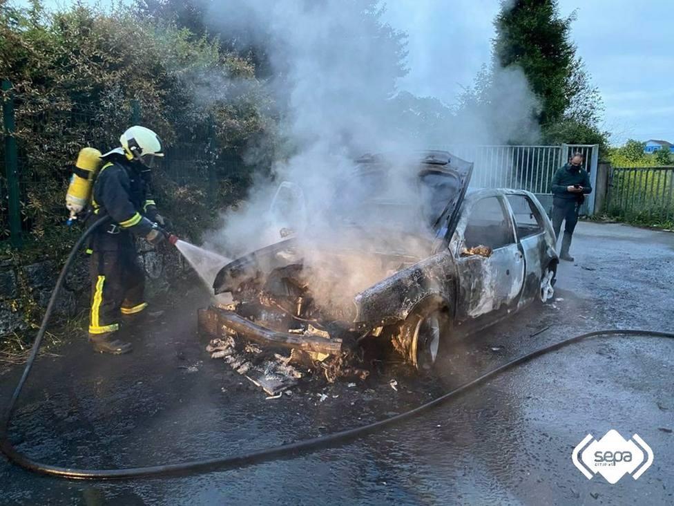 Bomberos apagando el incendio de un vehículo en Lugones