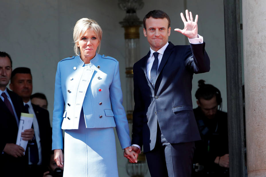 French President Emmanuel Macron and his wife Brigitte Trogneux wave to French President Francois Hollande as he leaves after the handover ceremony at the Elysee Palace in Paris