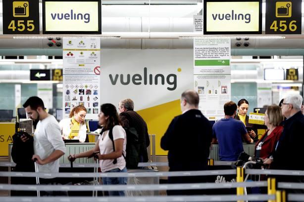 Un grupo de pasajeros ante un mostrador de facturacion de Vueling