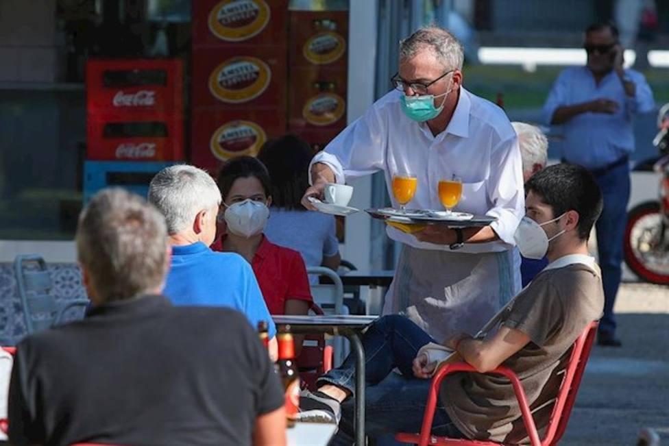 Un camarero sirve a los clientes en una terraza