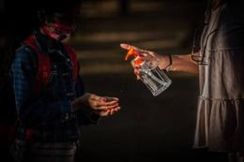 Una profesora administra gel desinfectante a un alumno